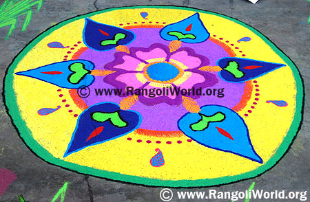 Freehand Rangoli with yellow color filling and pink flower in the middle
