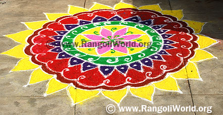 Freehand Rangoli with yellow leaves layer outline and pink flower in the middle